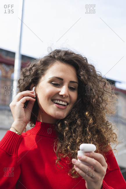 Happy woman connecting wireless in-ear headphones on sunny day