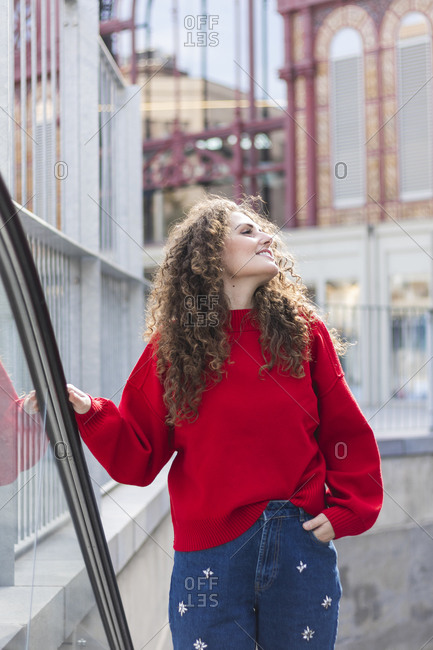 Beautiful young woman with hand in pocket looking away while moving up on escalator