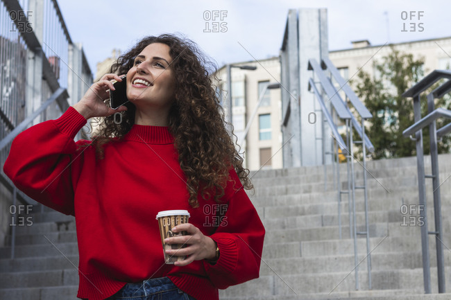 Smiling woman holding coffee cup while talking on mobile phone at staircase