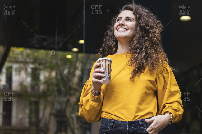 Happy businesswoman in yellow blouse holding disposable cup while looking up