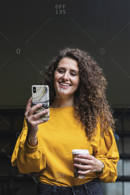 Happy businesswoman on video call through smart phone while holding disposable cup