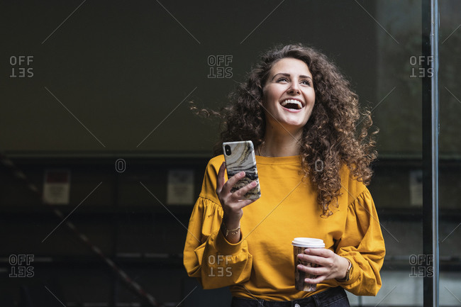 Cheerful female professional with curly hair laughing while holding mobile phone and disposable cup