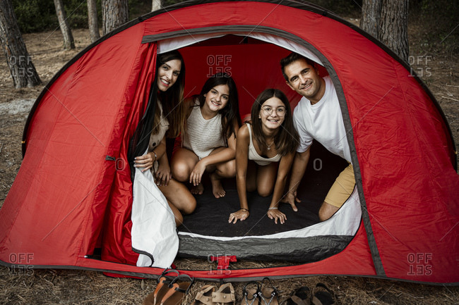 Smiling family spending leisure time in tent during vacation