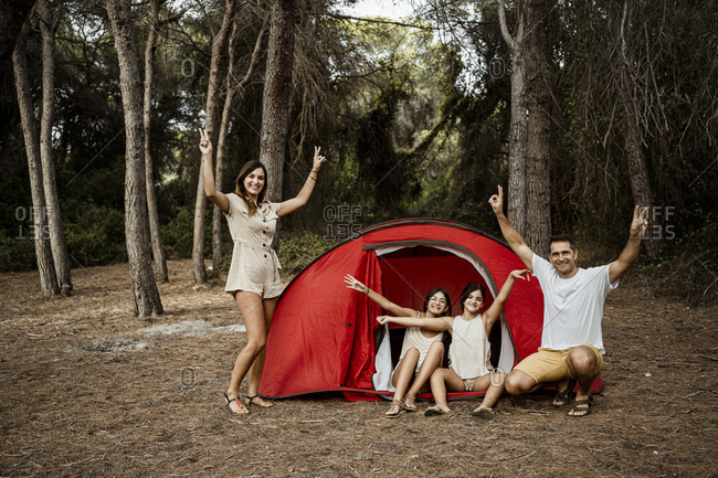 Happy parents and children doing peace sign during camping in forest