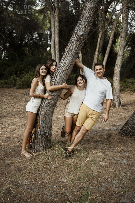 Family leaning on tree in forest during vacation