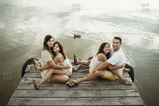 Daughters embracing mother and father while sitting on jetty against lake