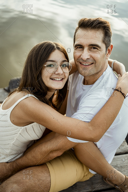 Smiling daughter embracing father while sitting at jetty