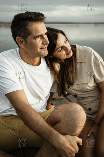 Mature woman leaning on man's shoulder while sitting at jetty