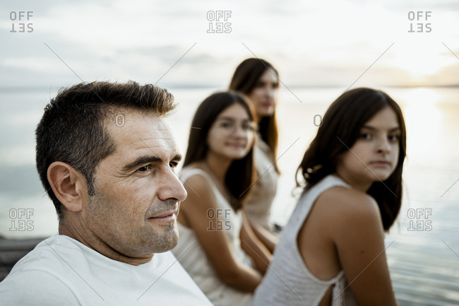 Father sitting with daughters and mother at jetty against lake