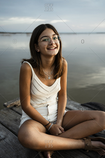 Girl with eyeglasses smiling while sitting on jetty against lake