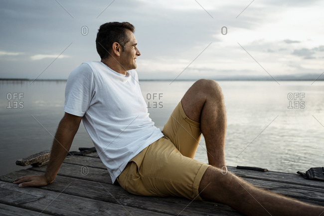 Mature man spending leisure time while sitting at jetty by lake against sky