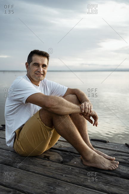 Smiling mature man sitting on jetty against lake