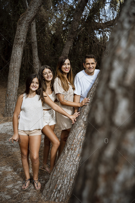 Parents with children standing behind tree trunk in forest