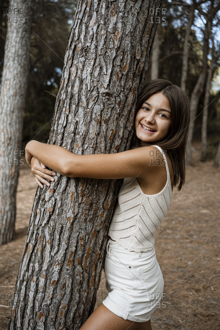 Smiling girl embracing tree trunk while standing in forest