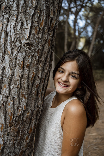 Smiling girl standing by tree trunk in forest during vacation