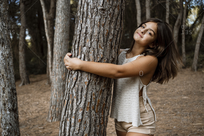 Girl embracing tree trunk while standing in forest during vacation