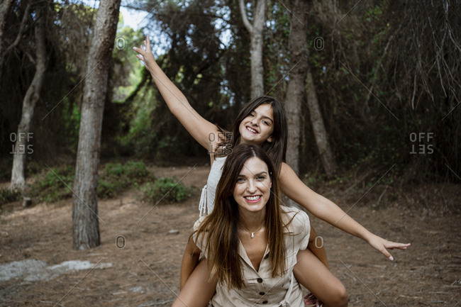 Mother giving piggyback ride to daughter in forest