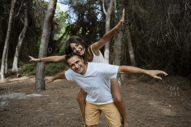 Smiling father giving piggyback ride to daughter with arms outstretched in forest during vacation