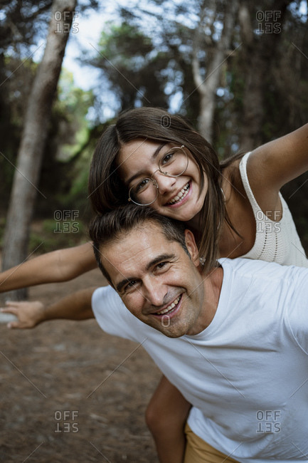 Father giving piggyback ride to daughter with arms outstretched in forest during vacation