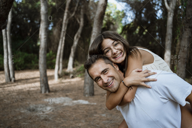 Happy father giving piggyback to daughter in forest