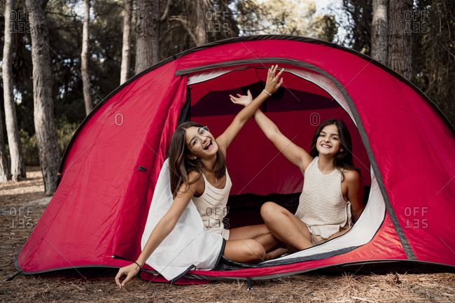 Cheerful sisters with hands raised sitting in tent at campsite during vacation
