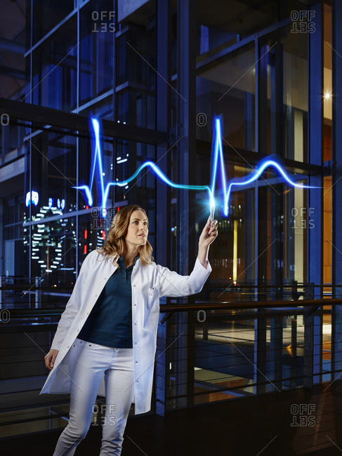 Female cardiologist examining pulse trace with light painting at hospital
