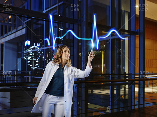 Female doctor examining pulse trace with light painting at hospital