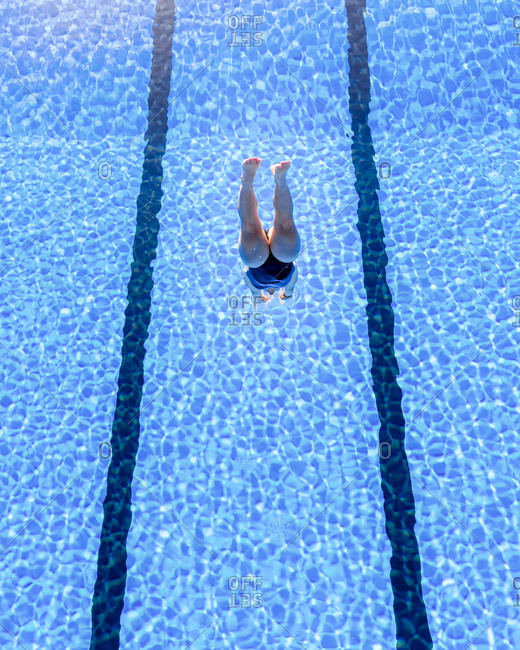 Young woman diving into swimming pool on sunny day