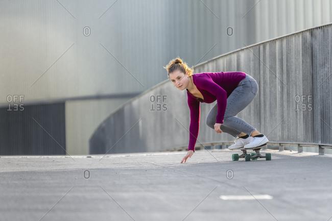 Young woman skateboarding on footbridge