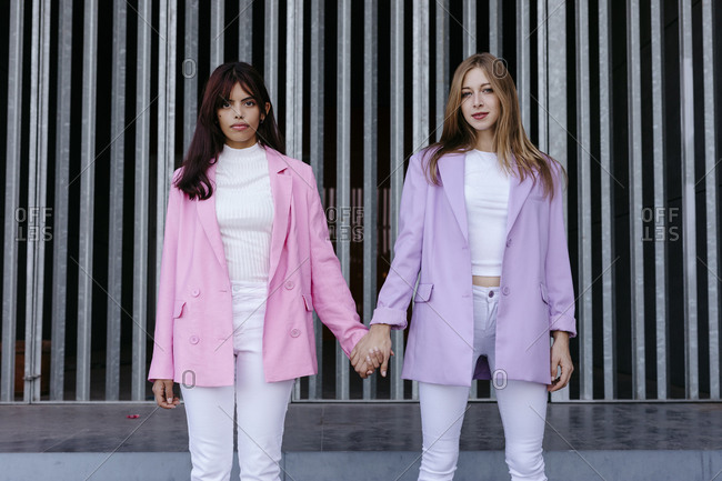 Sisters holding hands while standing against wall