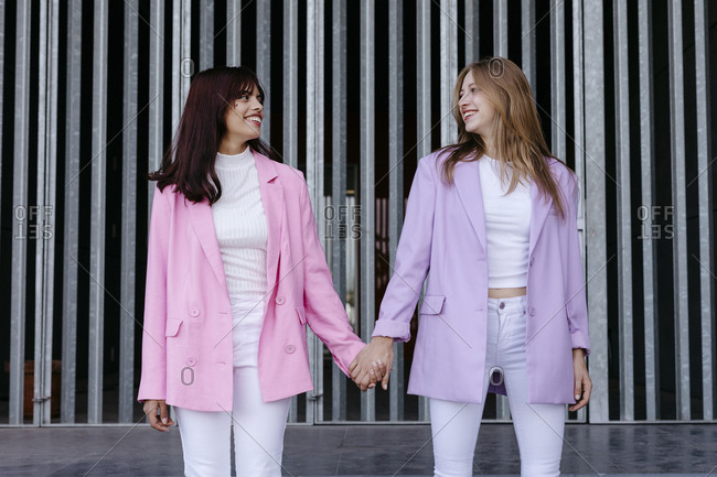 Smiling sisters holding hands while standing against wall