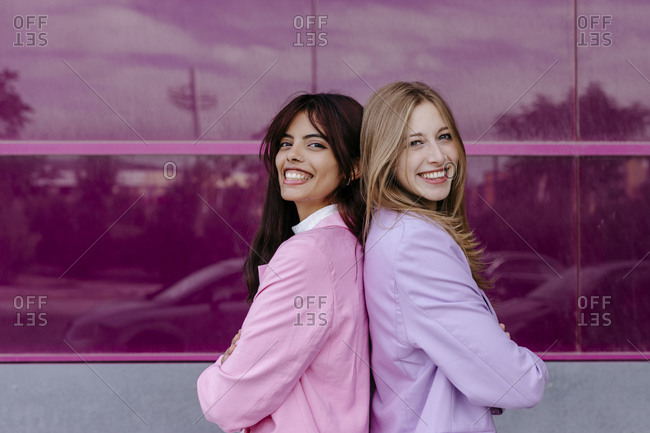 Smiling sisters standing back to back by acrylic glass wall