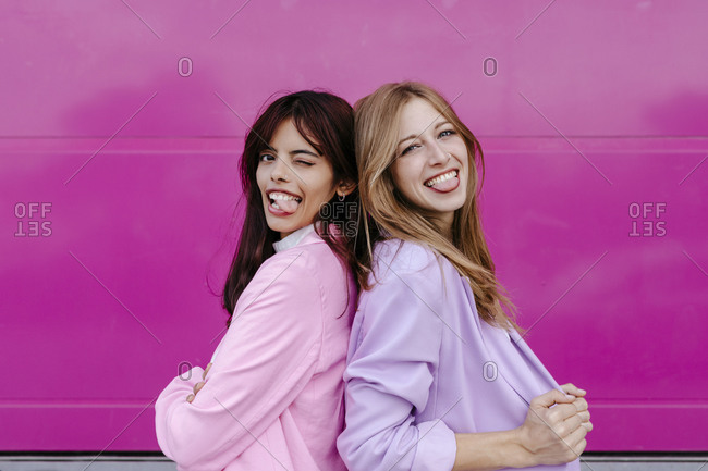 Sisters sticking out tongue while standing back to back by pink wall