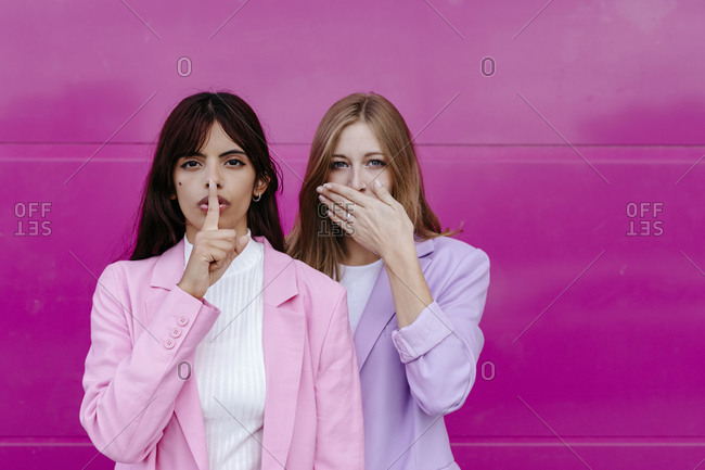 Young woman with finger on lips standing by sister covering mouth against pink wall