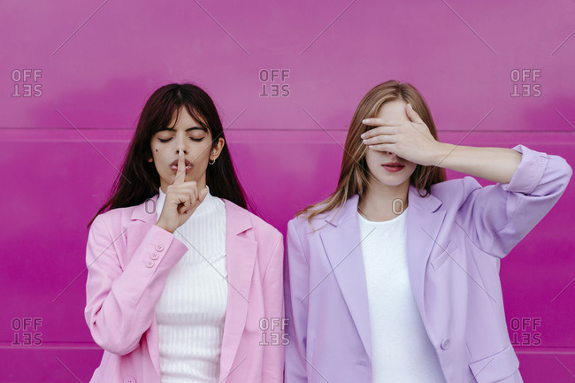 Young woman with finger on lips standing by sister covering eyes against pink wall