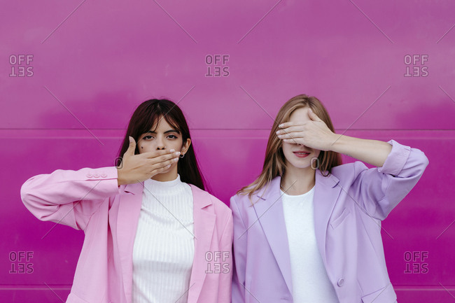 Sister with hand covering mouth standing by woman covering eyes against pink wall