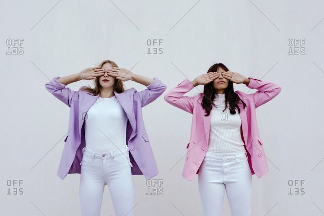 Sisters with hands covering eyes standing against white wall