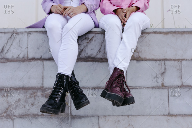 Sisters wearing boots sitting on retaining wall