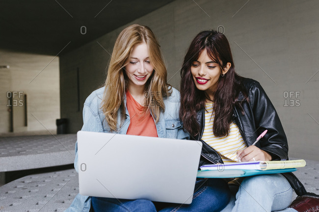 Young female student using laptop while studying together at university campus