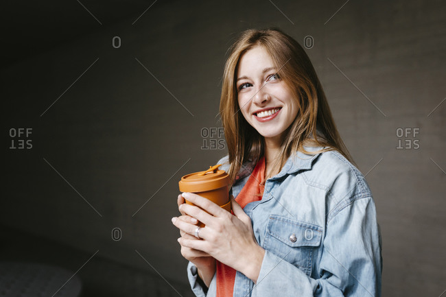 Happy beautiful young woman holding reusable coffee cup at university campus