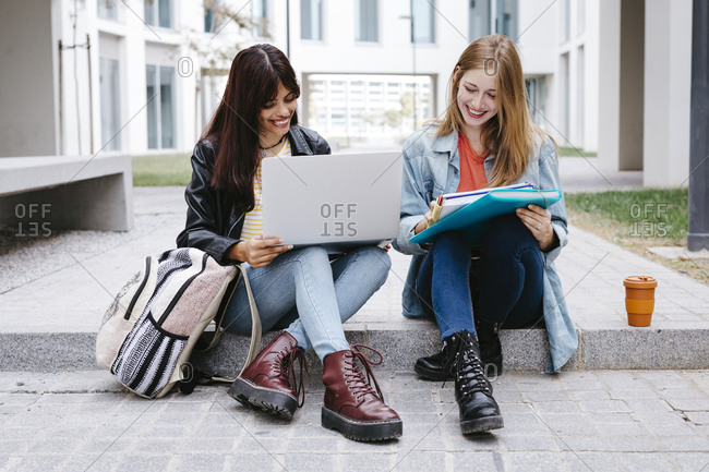 Female students studying on steps at university campus