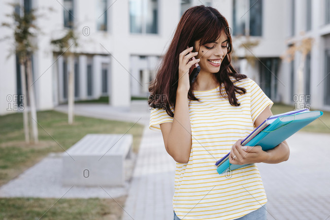 Smiling Latin female student talking on mobile phone while looking at books and file