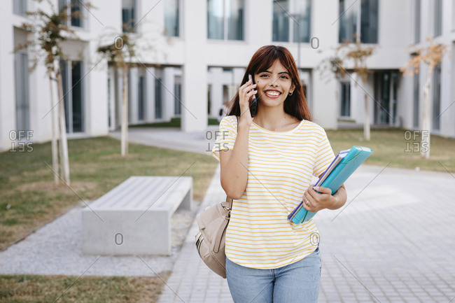 Smiling Hispanic female student talking on mobile phone while standing with books and file