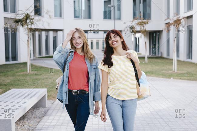 Happy young multi-ethnic female students walking around university campus