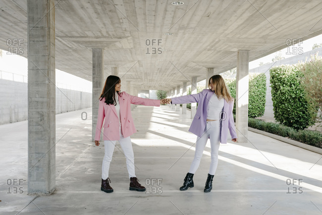 Young sisters holding hands standing in parking lot