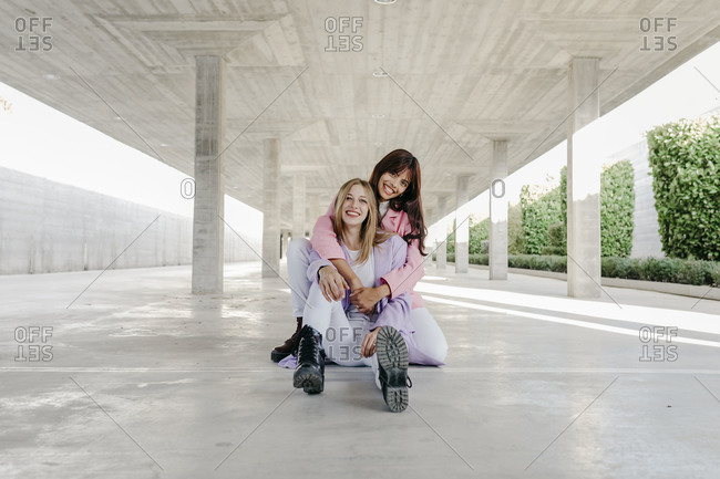 Smiling woman embracing sister on floor at parking lot