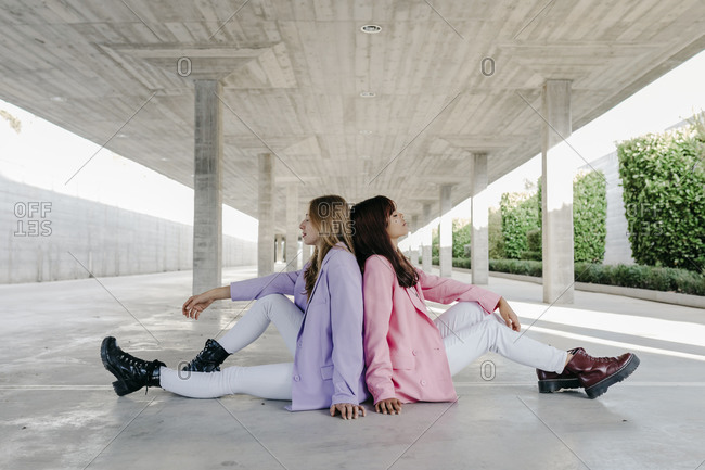 Young sisters sitting back to back on floor at parking lot