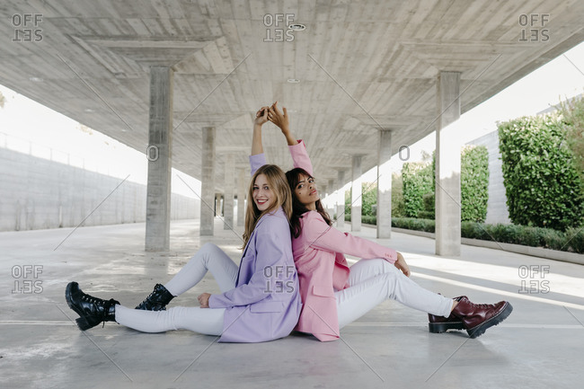 Trendy sisters with hand raised sitting back to back at parking lot