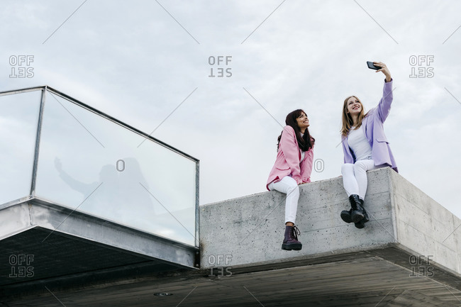 Sisters taking selfie through smart phone while sitting on rooftop in city against sky