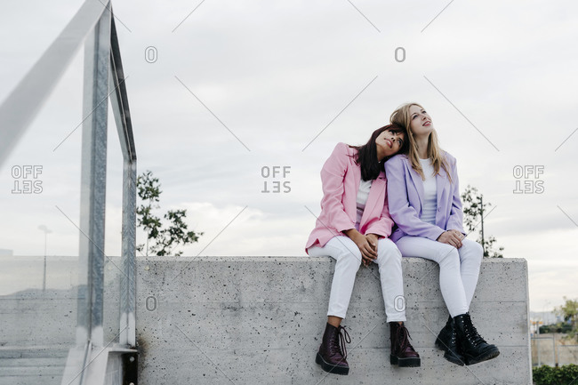 Young woman leaning on sister's shoulder while sitting on rooftop against sky in city